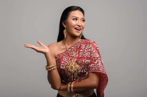 Schöne thailändische frau, die thailändisches kleid trägt