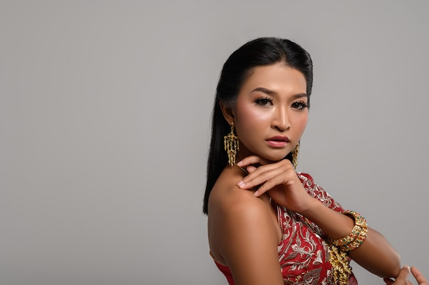 Schöne thailändische frau, die thailändisches kleid trägt und zur seite schaut Kostenlose Fotos