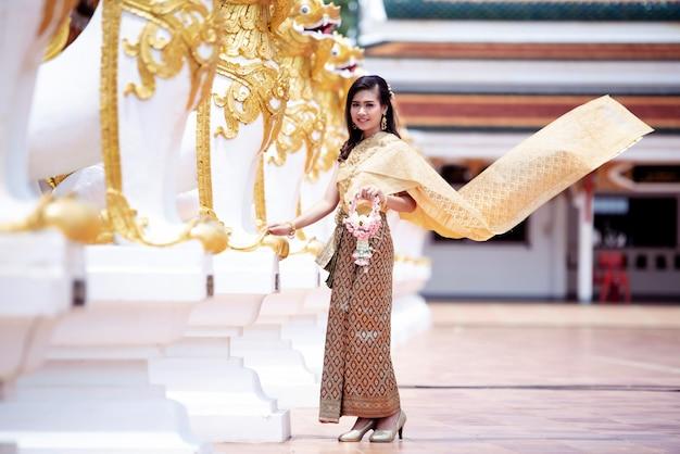 Schöne thailändische frau im thailändischen traditionellen kostüm am tempel Kostenlose Fotos