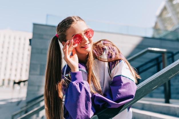 Schöne trendige junge frau in stilvollen kleidern, die mit lächeln aufwerfen Kostenlose Fotos