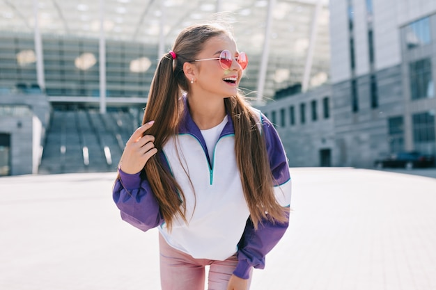 Schöne trendige junge frau in stilvollen kleidern, die rosa sonnenbrille tragen und lachen Kostenlose Fotos