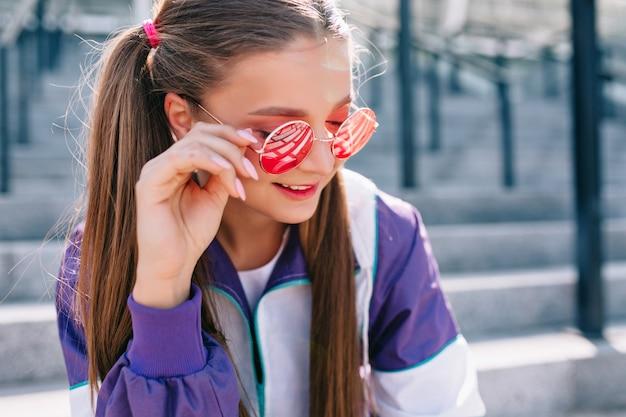 Schöne trendige junge frau in stilvollen kleidern, die rosa sonnenbrille tragen und lächeln Kostenlose Fotos