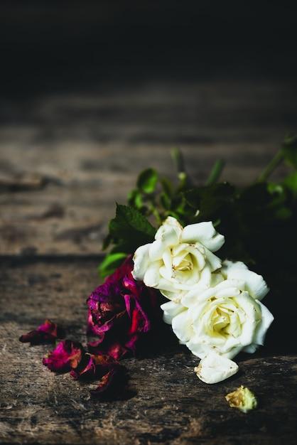 Schöne trockene rote und weiße rosen auf hölzernem