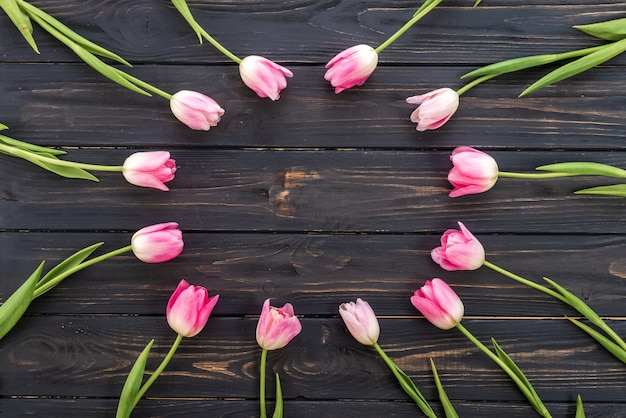 Schöne tulpen in der rosa pastellfarbe auf hölzernem hintergrund, draufsicht, rahmen, grenze. Premium Fotos