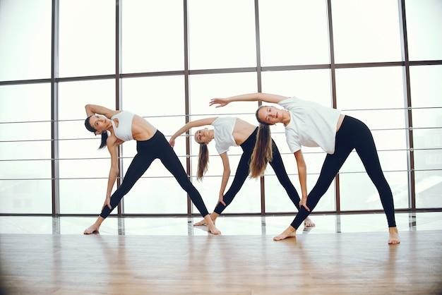 Schöne und elegante mädchen, die yoga tun Kostenlose Fotos