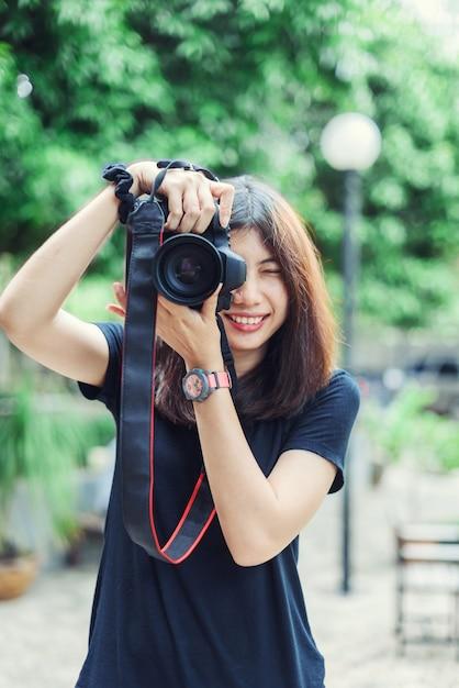 Schöne und glückliche asiatin, die kamera im garten hält. Premium Fotos