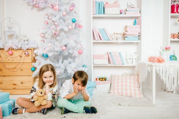 Schöne und lustige kinder, die für kamera in einem kinderraum mit winterurlaubdekorationen aufwerfen. Premium Fotos