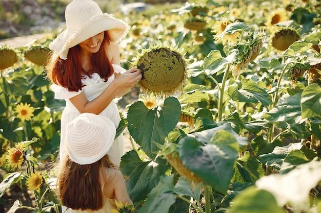 Schöne und nette familie auf einem gebiet mit sonnenblumen Kostenlose Fotos