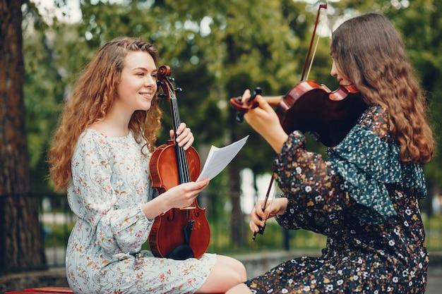 Schöne und romantische mädchen in einem park mit einer violine Kostenlose Fotos