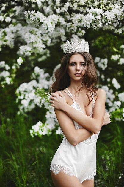 Schöne und sexy junge modellfrau mit perfektem körper in stilvollen dessous mit der krone auf ihrem kopf, die unter dem blühenden baum am grünen wald aufwirft Premium Fotos
