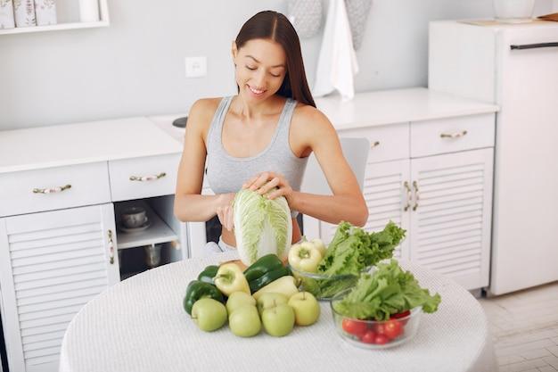 Schöne und sportliche frau in einer küche mit gemüse Kostenlose Fotos