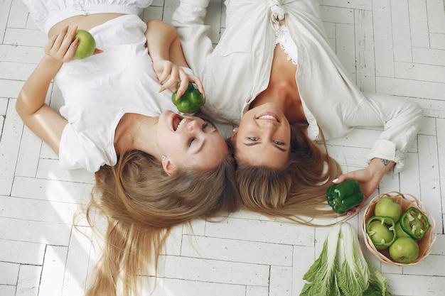 Schöne und sportliche frauen in einer küche mit gemüse Kostenlose Fotos
