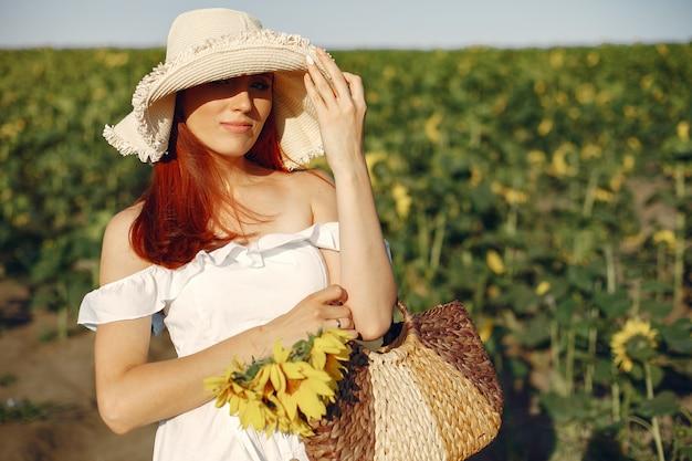 Schöne und stilvolle frau auf einem gebiet mit sonnenblumen Kostenlose Fotos