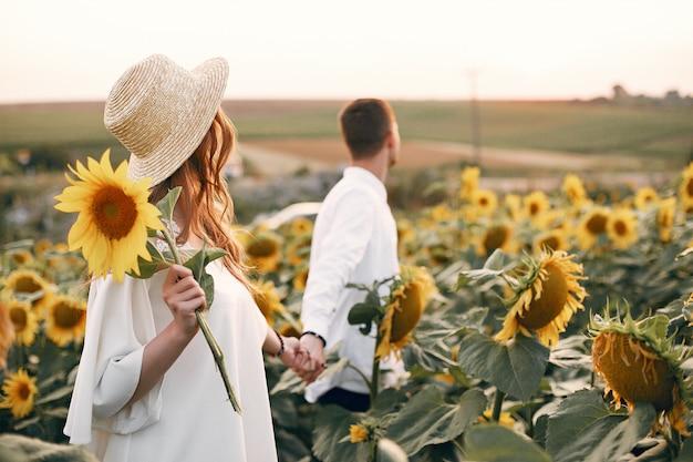 Schöne und stilvolle paare auf einem gebiet mit sonnenblumen Kostenlose Fotos
