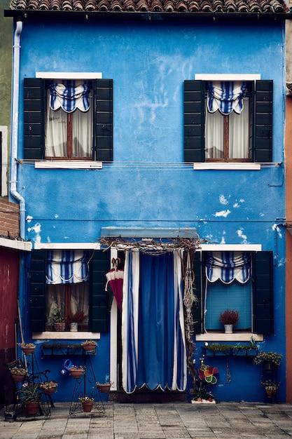 Schöne vertikale symmetrische aufnahme eines vorstädtischen blauen gebäudes mit pflanzen in töpfen Kostenlose Fotos