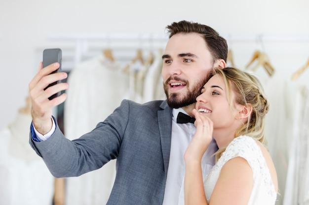 Schöne vorbildliche hochzeitspaare, die smartphone on-line-videoanruf betrachtet schirm halten Premium Fotos