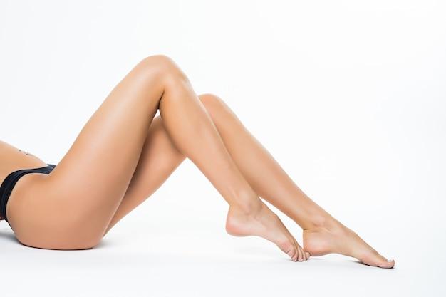 Schöne weibliche beine, arschrückenkörper lokalisiert über weißer wand, die auf dem boden mit langem bein, beauty spa und hautpflegekonzept liegt. Kostenlose Fotos