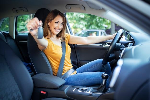 Schöne weibliche fahrerinnen sitzen in ihrem fahrzeug und halten autoschlüssel bereit für eine fahrt Kostenlose Fotos