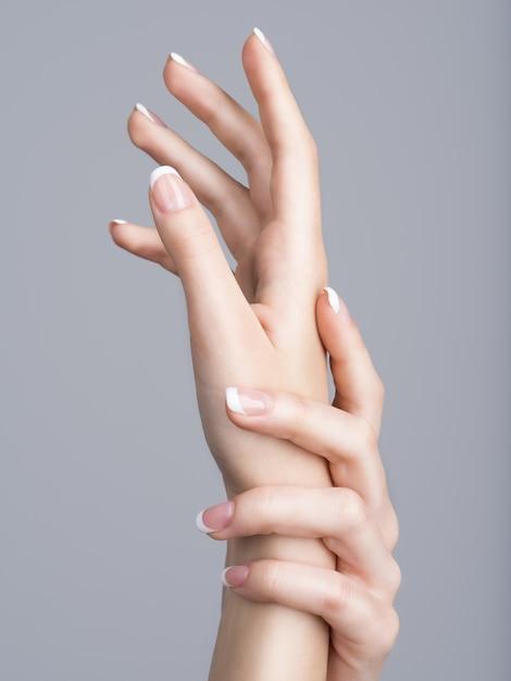 Schöne weibliche hände mit französischer maniküre auf nägeln Kostenlose Fotos