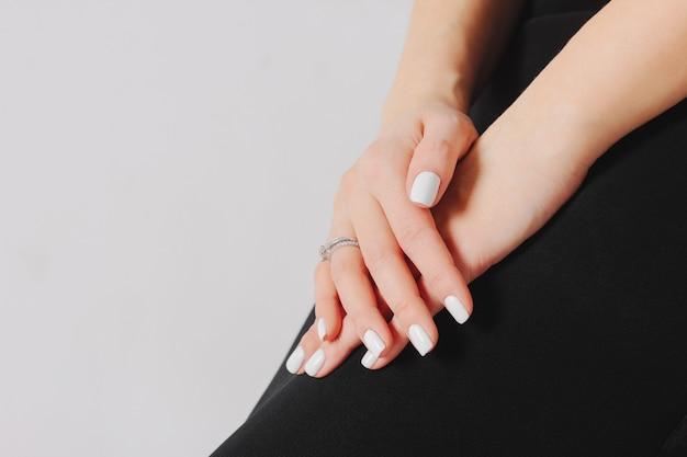 Schöne weibliche hände mit weißer maniküre und verlobungsring, Premium Fotos
