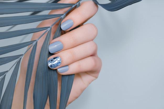 Schöne weibliche hand mit blauem nagel Premium Fotos
