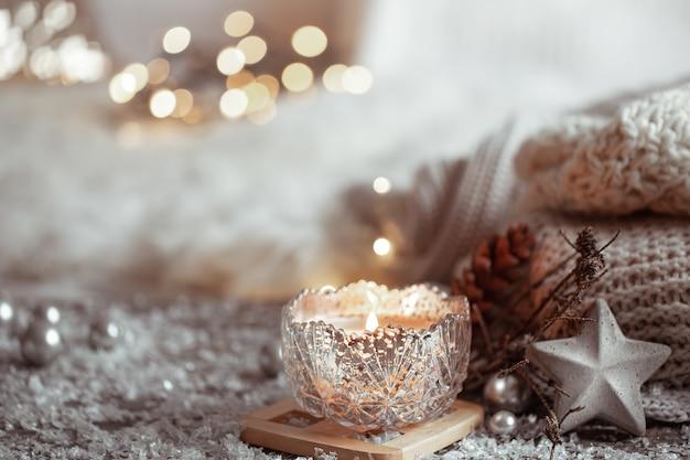 Schöne weihnachtskerze in einem kerzenhalter auf einem hellen unscharfen hintergrund. das konzept von wohnkomfort und wärme. Kostenlose Fotos