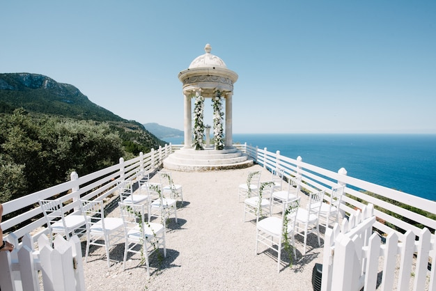 Schöne weiße hochzeitszeremonie auf dem berg durch das meer Premium Fotos