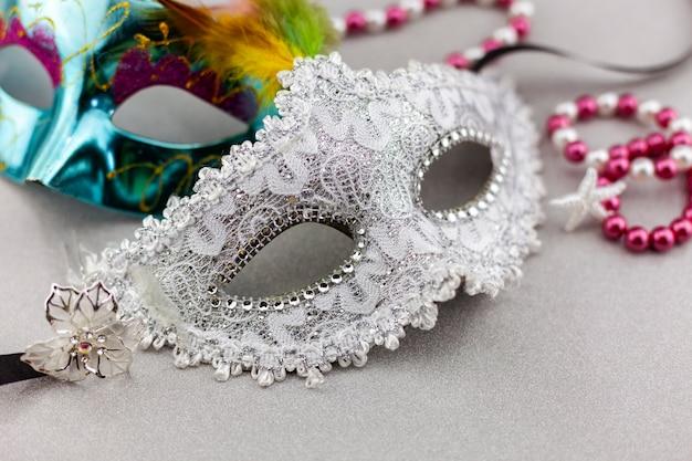 Schöne weiße karnevals- oder karnevalsmaske auf schönem buntem papierhintergrund Premium Fotos