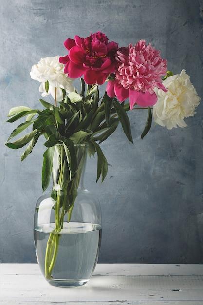 Schöne weiße, lila und rosa pfingstrosenblumen in einer glasvase. Premium Fotos