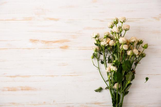 Schöne weiße rosen auf holztisch Kostenlose Fotos