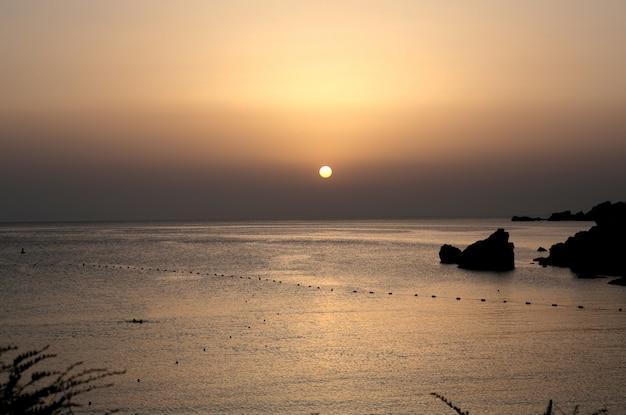 Schöne weite aufnahme eines ozeans während der morgendämmerung mit rosa himmel Kostenlose Fotos