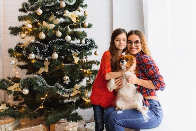Schöne winterferien! positive brünette frau umarmt pose des kleinen mädchens mit geschenken auf dem boden im zimmer, hund nahe, haben spaß nahe weihnachtsbaum. Premium Fotos