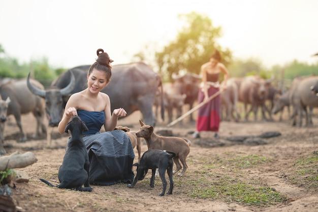 Schöne zwei asiatische frauen, die im traditionellen kostüm mit büffel am ackerland gekleidet werden, man sitzen auf spiel des erdgeschosses mit hunden und man verwenden spatengrabungsboden. Premium Fotos