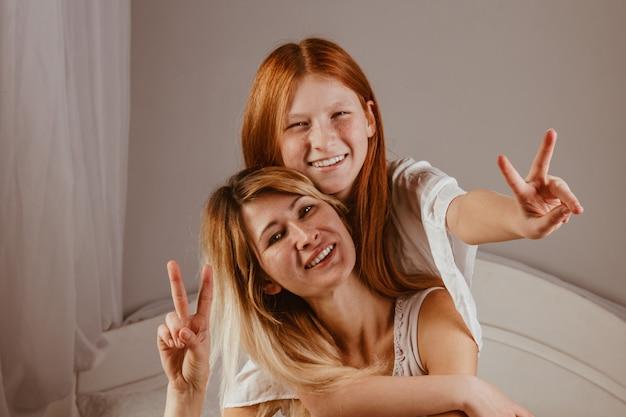 Schönen muttertag. mutter und tochter spielen mädchen, lächeln und umarmen sich im bett. familienurlaub und zusammensein. Premium Fotos