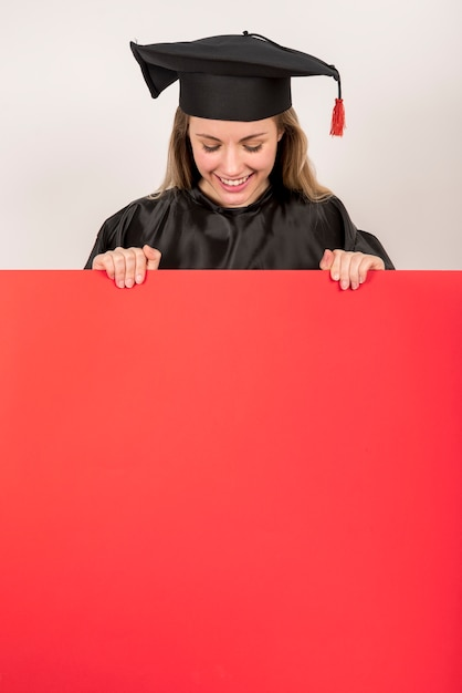 Schöner absolvent, der rotes plakatmodell hält Kostenlose Fotos