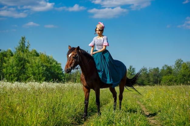 Schöner aristokrat in einem kleid auf einem pferd Premium Fotos