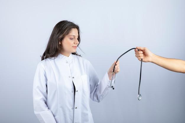 Schöner arzt im weißen kittel, der stethoskop von einer anderen person nimmt. Kostenlose Fotos