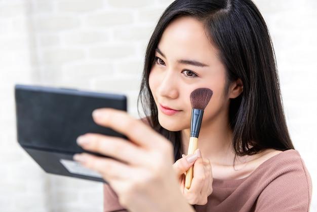 Schöner asiatinschönheit blogger, der make-uptutorial tut Premium Fotos