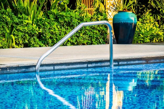 Schöner außenpool mit liegestuhl und sonnenschirm im resort für reisen und urlaub Kostenlose Fotos