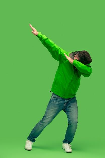 Schöner bärtiger junger mann, der kamera lokalisiert auf grün betrachtet Kostenlose Fotos