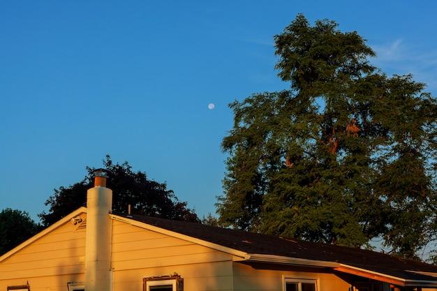 Schöner blauer himmel und mond über dem dachhaus Premium Fotos