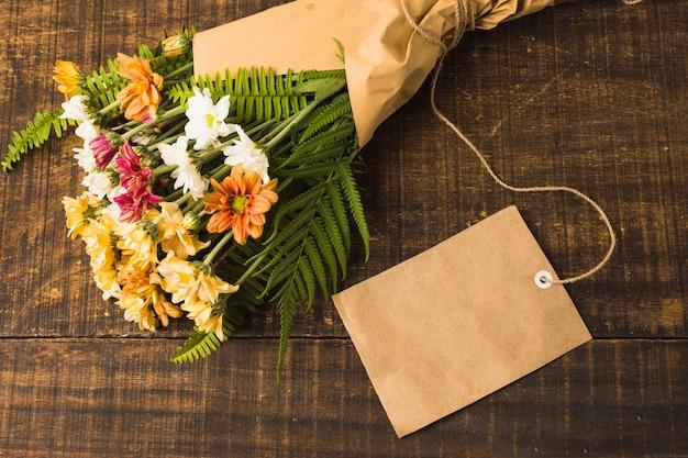 Schöner blumenblumenstrauß mit leerem aufkleber über hölzernem schreibtisch Kostenlose Fotos