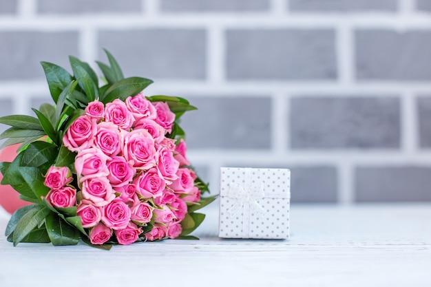 Schöner blumenstrauß aus rosen für grüße. geschenkbox. konzept happ Premium Fotos