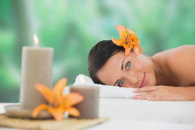 Schöner brunette, der auf der massagetabelle lächelt an der kamera sich entspannt Premium Fotos