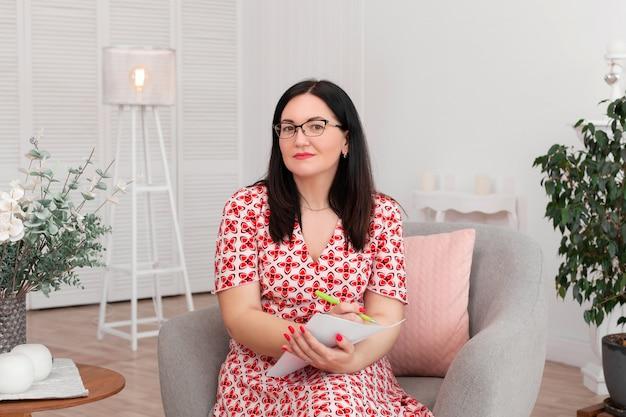 Schöner brunetteärztin-psychologe mit gläsern sitzend in einem hellen büro, das auf papier lächelt und schreibt Premium Fotos