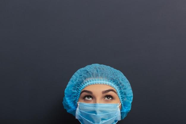 Schöner doktor im weißen medizinischen kleid, in der kappe und in der maske. Premium Fotos