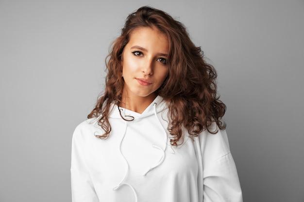 Schöner frauenjugendlicher im weißen hoodie, der über einem grauen hintergrund aufwirft Premium Fotos