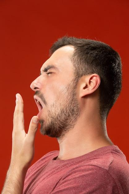 Schöner gelangweilter mann gelangweilt lokalisiert auf roter wand Kostenlose Fotos