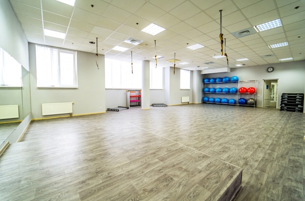 Schöner geräumiger fitnessraum für fitnesstraining mit sportgeräten. Premium Fotos