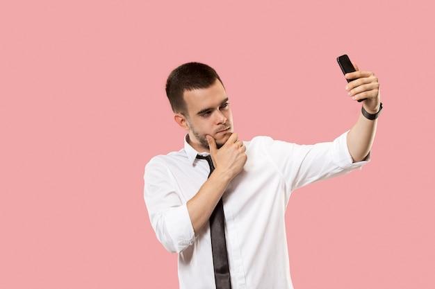 Schöner geschäftsmann mit handy. der junge geschäftsmann, der steht und selfie-foto lokalisiert auf rosa studiohintergrund macht. Kostenlose Fotos
